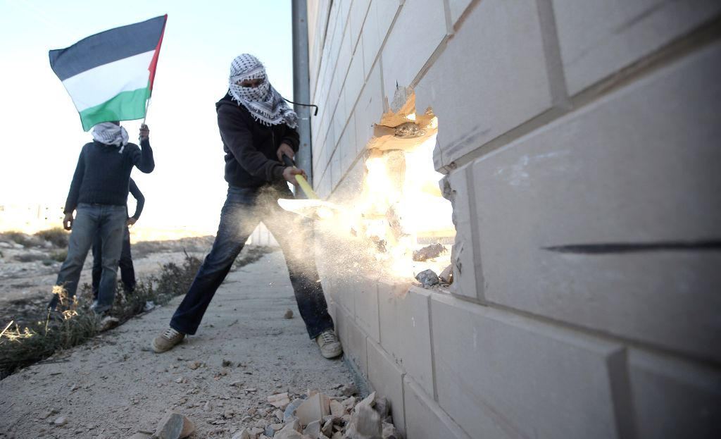 Palestinian activists demolish a section of Israeli apartheid wall viewing a highway between Jerusalem and Tel Aviv near Ramallah as they mark the 25th anniversary of Berlin wall memorial ..