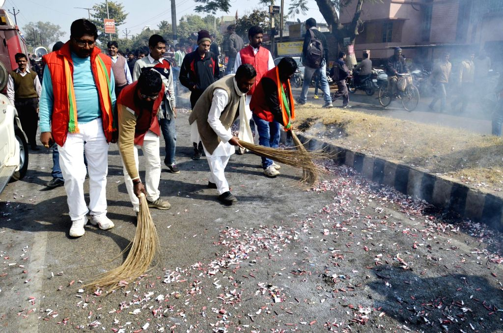 BJP workers sweep a road after bursting fire crackers as the party leads in Jharkhand Assembly polls in Ranchi on Dec 23, 2014.