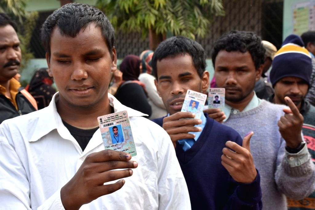 Ranchi: Blind voters show inked mark finger and their special Election Identity Cards after casting their vote in a special Brail EVM machine organized by Election Commission during 3rd phase of Jharkhand Assembly Election in Ranchi on Dec. 12, 2019.
