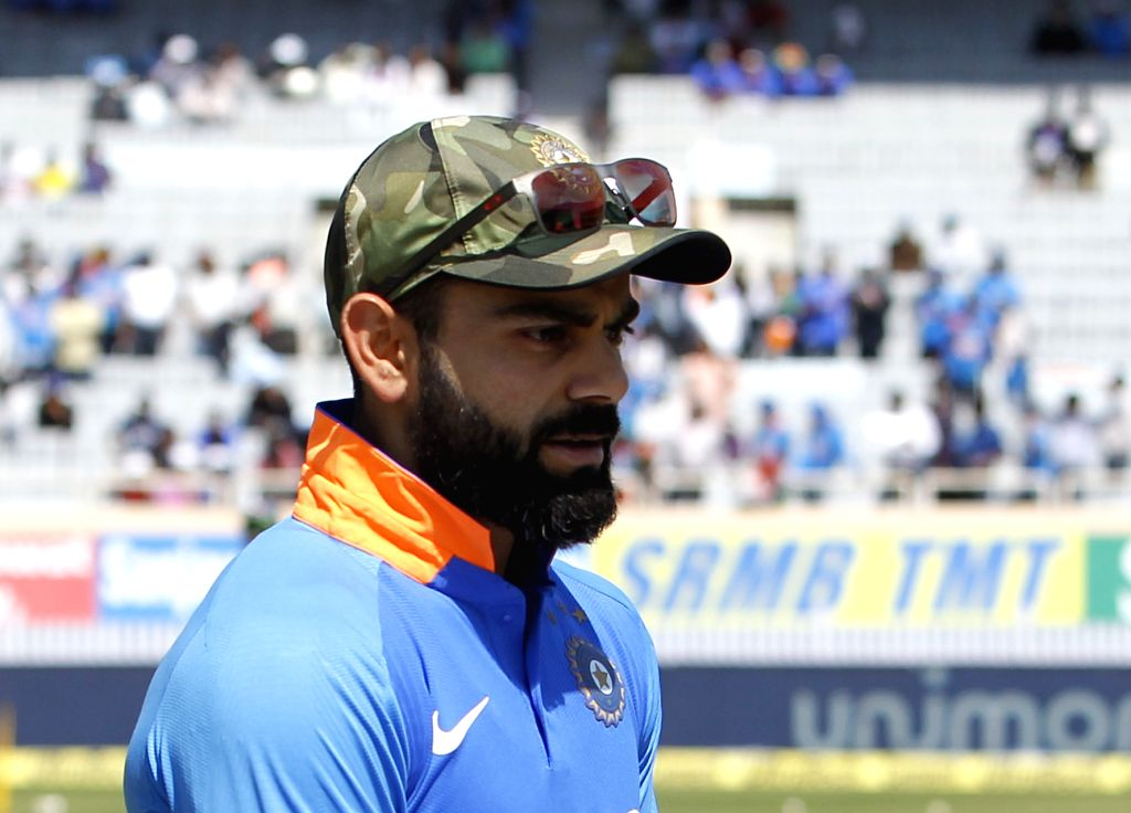 Ranchi: India's Virat Kohli dons a camouflage cap during the third ODI match against Australia at JSCA International Stadium Complex in Ranchi on March 8, 2019. 'Men in Blue' are wearing the camouflaged caps to pay tribute to the Indian Armed Forces. - Virat Kohli and Surjeet Yadav