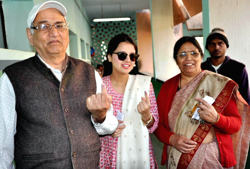 Indian cricket captain Mahendra Singh Dhoni's father Paan Singh, mother and wife Shakshi show their fore-fingers marked with phosphorous ink after casting their votes during the third phase .. - Mahendra Singh Dhon and Paan Singh