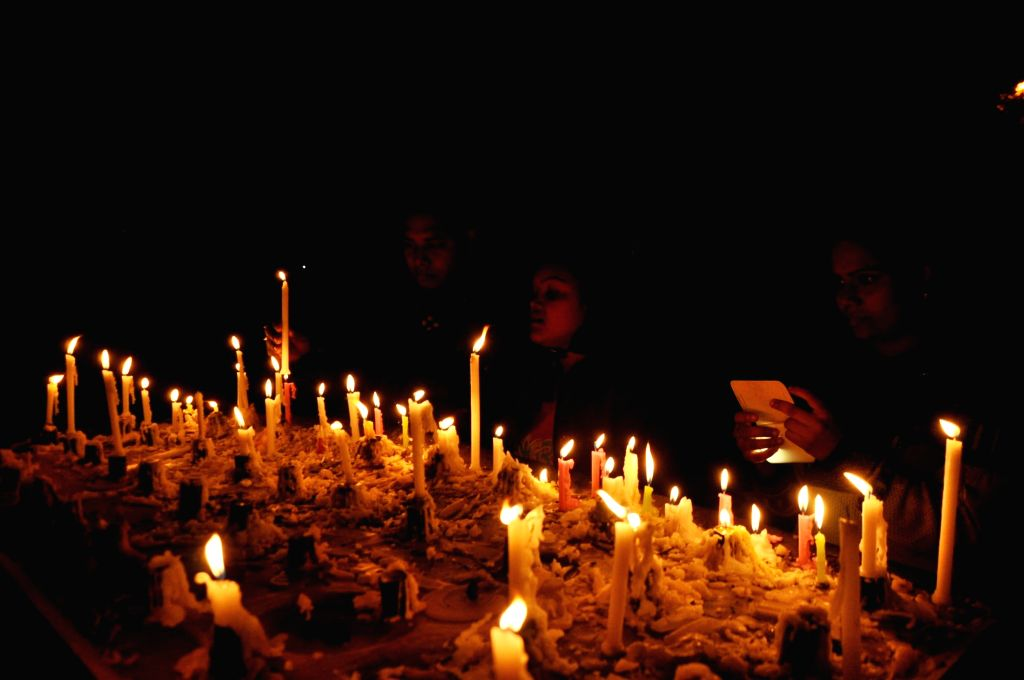 People light a candles on Christmas eve at a Ranchi Church on Dec 24, 2014.
