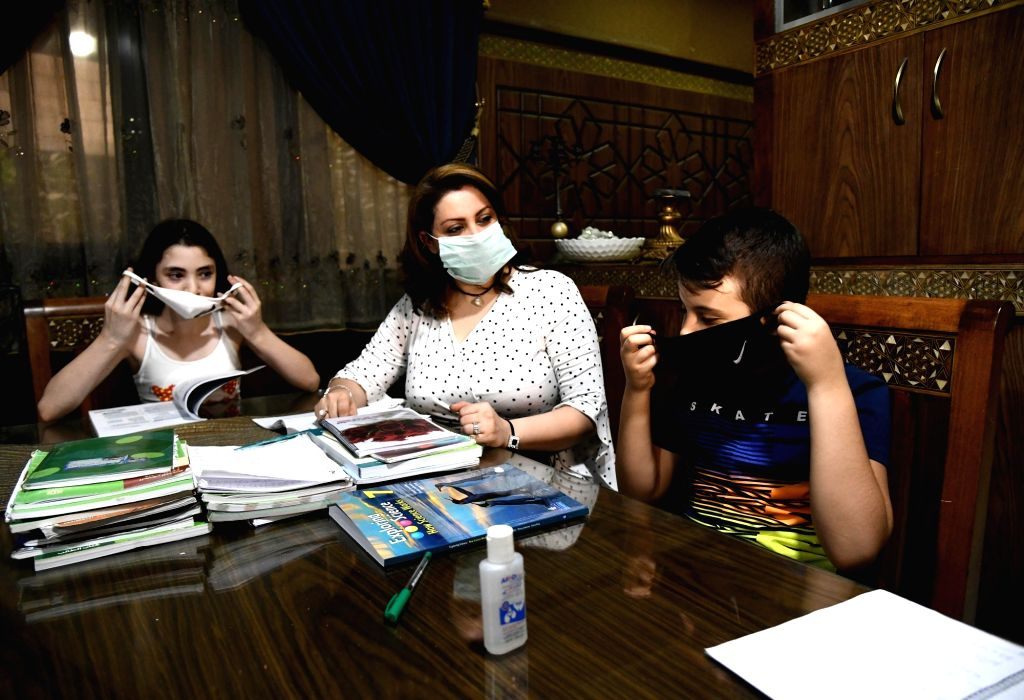 Rania al-Halabi (C) looks on as her children practise to wear face masks at home in Damascus, capital of Syria, Sept. 10, 2020. Instead of helping her son review ...
