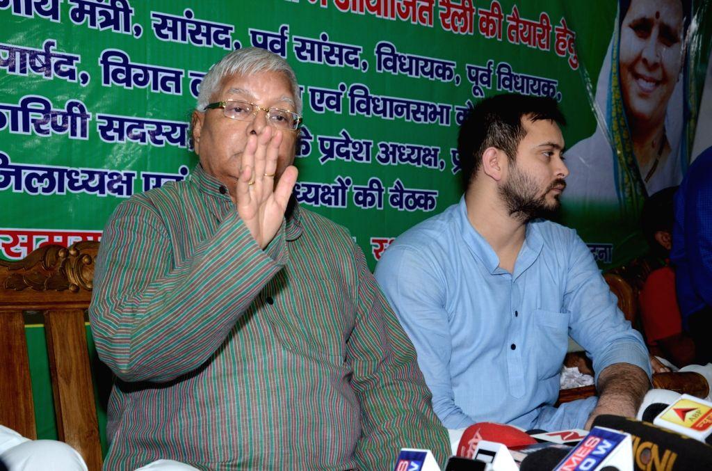 Rashtriya Janata Dal (RJD) Supremo Lalu Prasad Yadav addresses a press conference after the Central Bureau of Investigation carried out raids at 12 places in Patna, Delhi, Ranchi, Puri and ... - Lalu Prasad Yadav and Tejashwi Yadav
