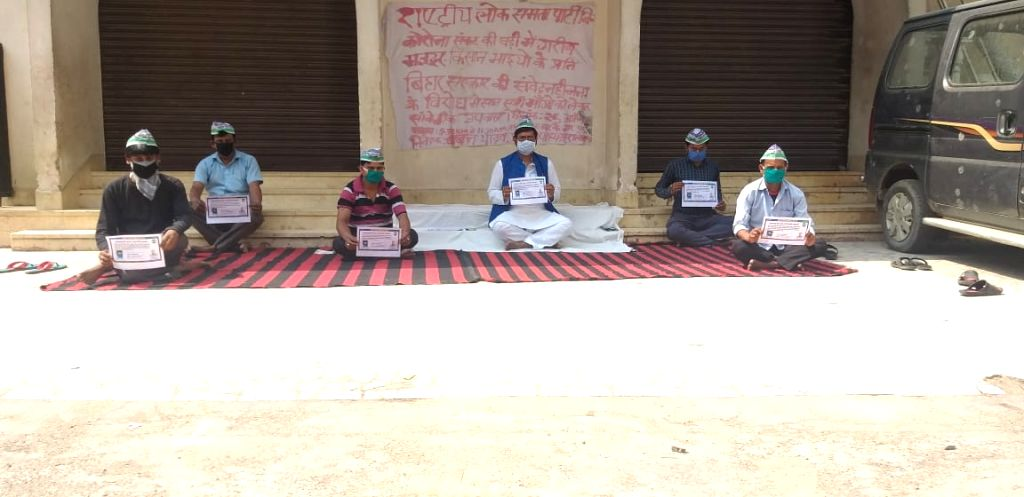 Rashtriya Lok Samta Party (RLSP) workers practise social distancing as they stage a sit-in demonstration to press fir their various demands in Patna during the extended nationwide lockdown ...