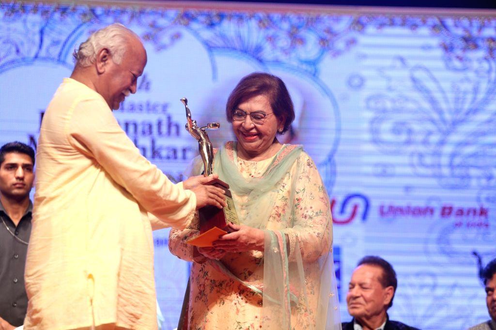 Rashtriya Swayamsevak Sangh (RSS) chief Mohan Bhagwat presents an award to veteran actress Helen during 2019 Deenanath Mangeshkar Awards, in Mumbai, on April 24, 2019. - Helen