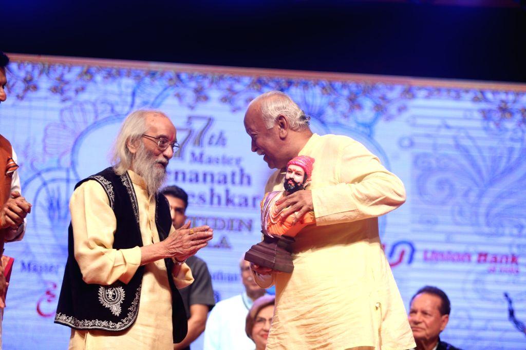 Rashtriya Swayamsevak Sangh (RSS) chief Mohan Bhagwat presents an award to writer Shivshahir Babasaheb Purandare during the 2019 Deenanath Mangeshkar Awards, in Mumbai, on April 24, 2019.