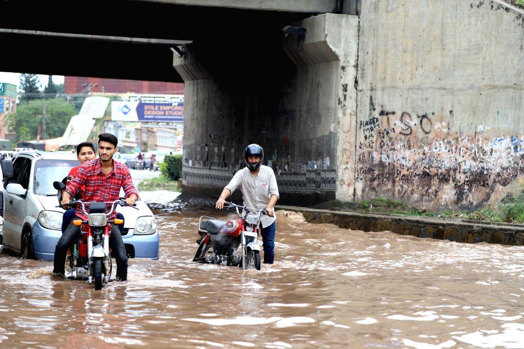 RAWALPINDI, July 25, 2019 - People push their bikes in flood water after heavy monsoon rain in Rawalpindi, Pakistan, July 25, 2019.