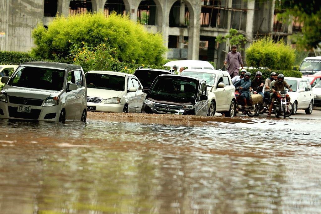 RAWALPINDI, July 25, 2019 - Vehicles move in flood water after heavy monsoon rain in Rawalpindi, Pakistan, July 25, 2019.