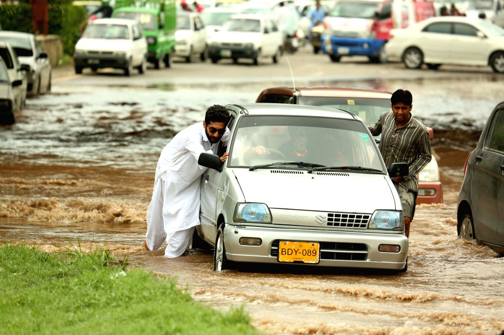RAWALPINDI, July 25, 2019 (Xinhua) -- People push a car as it stuck in flood water after heavy monsoon rain in Rawalpindi, Pakistan, July 25, 2019. (Xinhua/Ahmad Kamal/IANS)