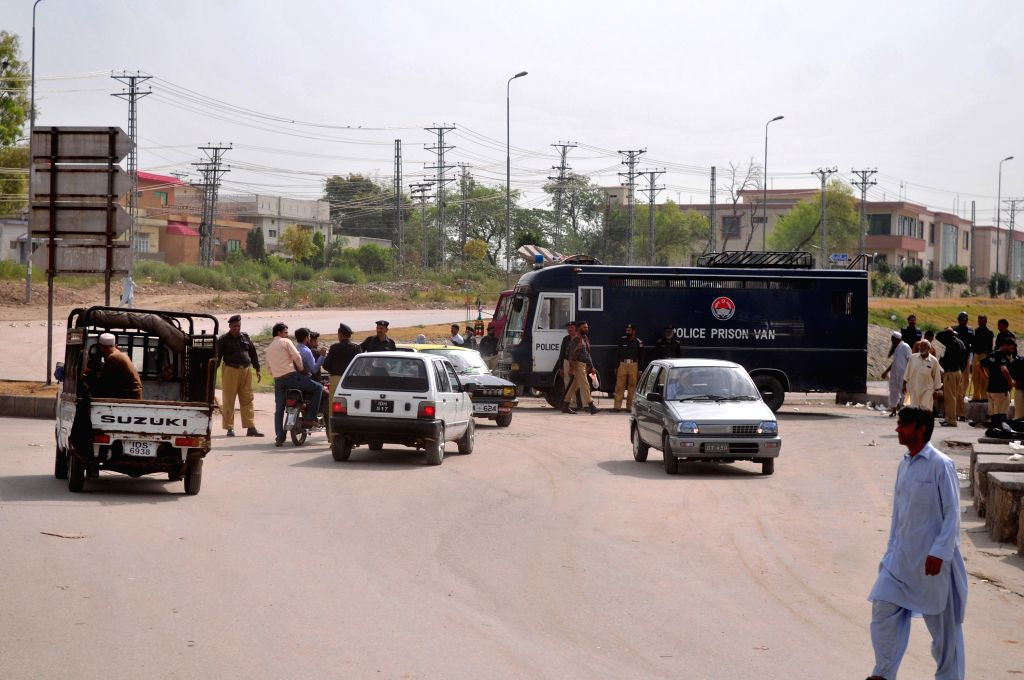 Policemen stop vehicles on the way to Islamabad airport in Rawalpindi, Pakistan, June 23, 2014. Pakistani authorities on Monday denied permission to a plane ...