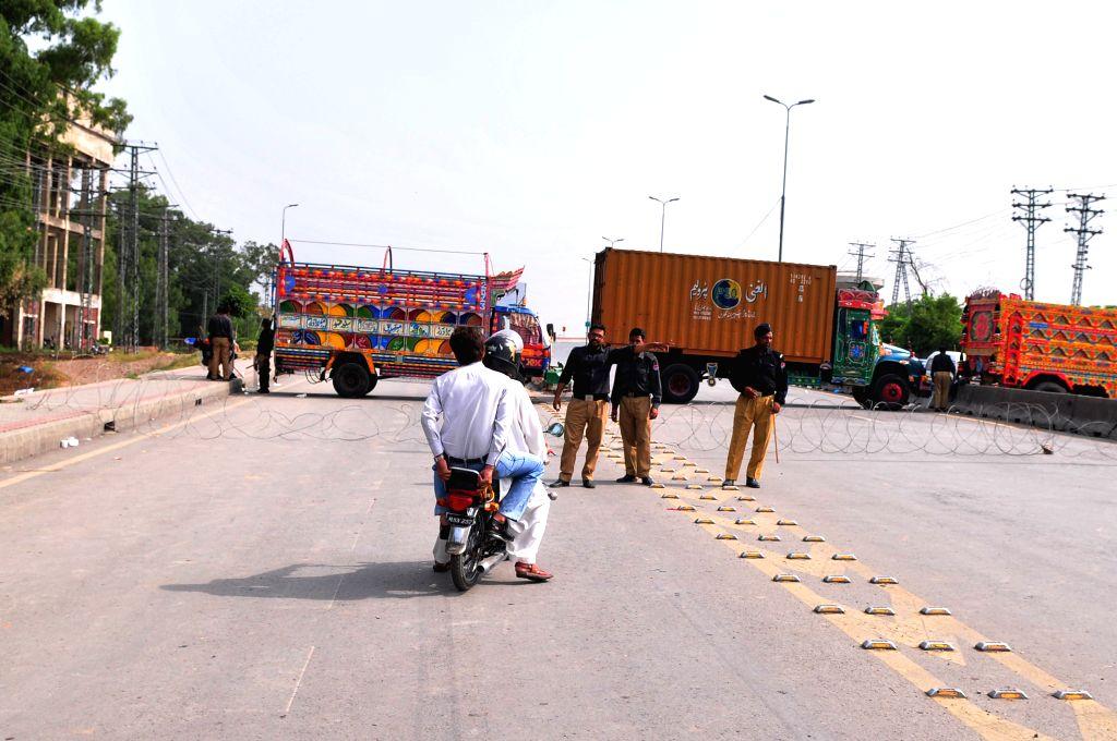 Policemen stop motorbike riders near trucks used to block a road leading to Islamabad airport in Rawalpindi, Pakistan, June 23, 2014. Pakistani authorities on ...