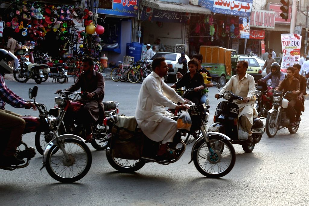 RAWALPINDI, Oct. 11, 2017 - People ride motorbikes in Rawalpindi, Pakistan, Oct. 11, 2017. The production of motorcycles in Pakistan surged by 34.81 percent during the first two months of the new ...