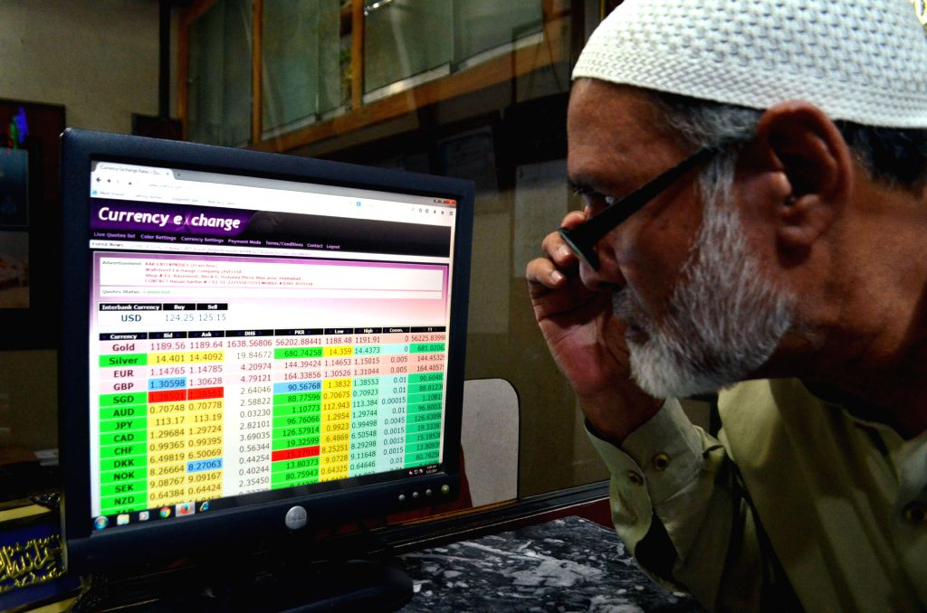 RAWALPINDI, Oct. 9, 2018 (Xinhua) -- A Pakistani man monitors foreign currency rates on a computer screen at a currency exchange shop in Rawalpindi, Pakistan on Oct. 9, 2018. The Pakistani rupee was in free fall in the interbank market on Tuesday, wi