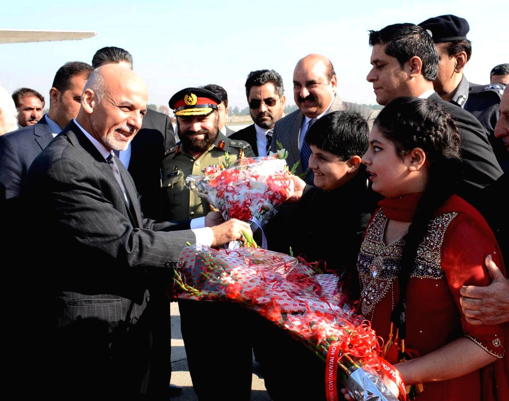Photo released by Press Information Department (PID) on Nov. 14, 2014 shows Afghan President Ashraf Ghani (L) receiving a bouquet from a Pakistani youth upon his arrival at the Nur Khan .. - Nur Khan