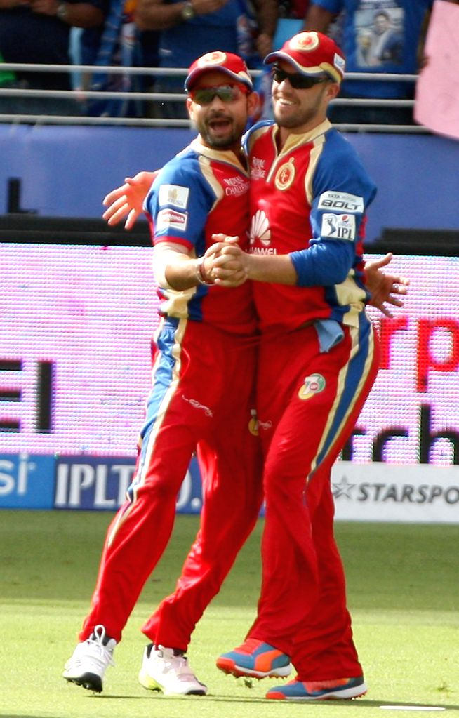 RCB players Virat Kohli and AB de Villiers celebrate fall of a wicket during the fifth match of IPL 2014 between Royal Challengers Bangalore and Mumbai Indians, played at Dubai International Cricket . - Virat Kohli
