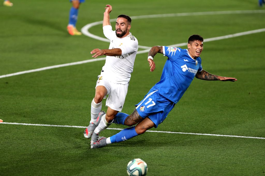 Real Madrid's Dani Carvajal (L) vies with Getafe's Mathias Olivera during a Spanish league football match between Real Madrid and Getafe in Madrid, Spain, July 2, ...