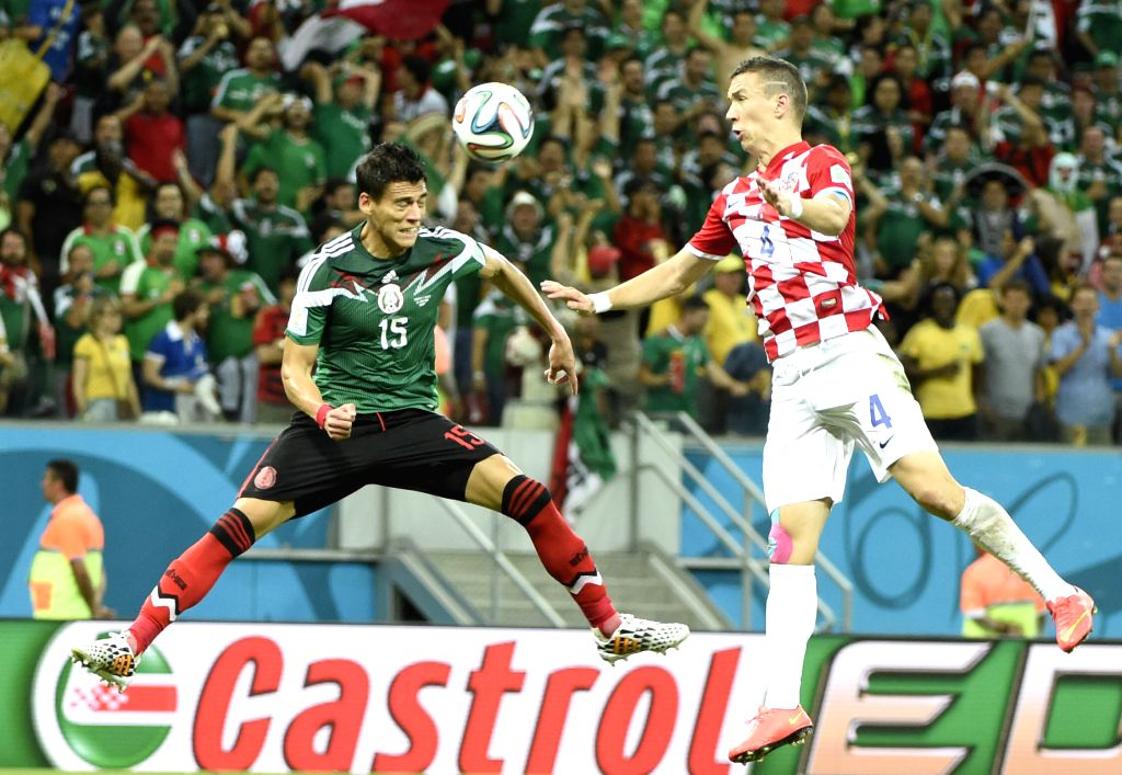 Mexico's Hector Moreno (L) competes with Croatia's Ivan Perisic during a Group A match between Croatia and Mexico of 2014 FIFA World Cup at the Arena Pernambuco ...
