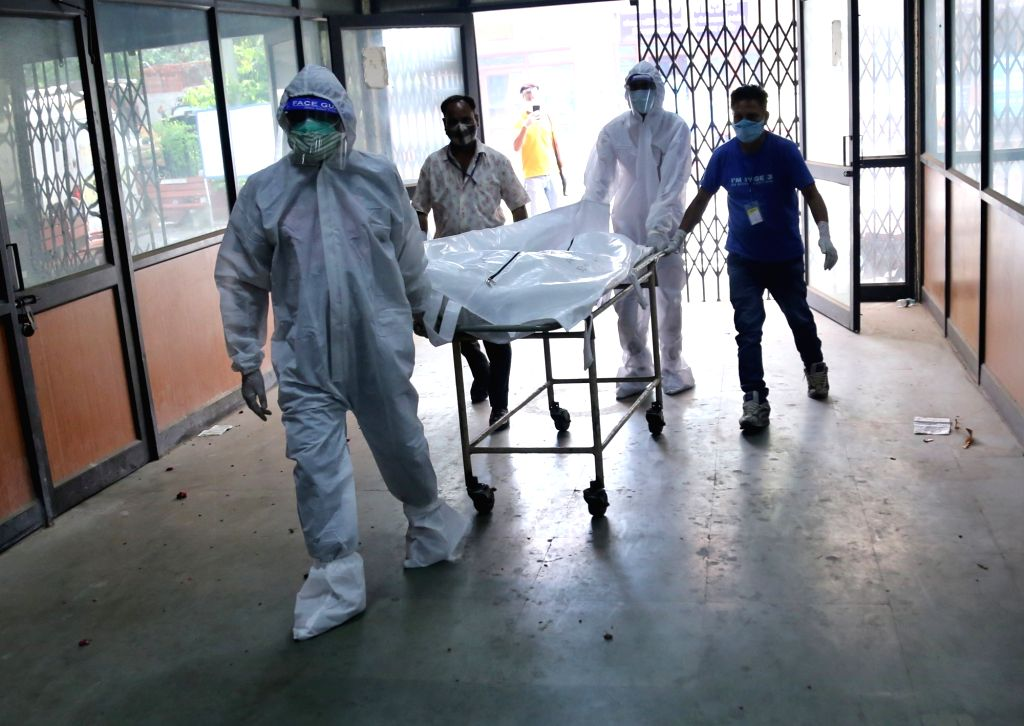 Relatives and Health workers cremation of the body of covid-19 affected victims for last rites at Nigambodh ghat crematorium in New Delhi on Wednesday, May 12, 2021.