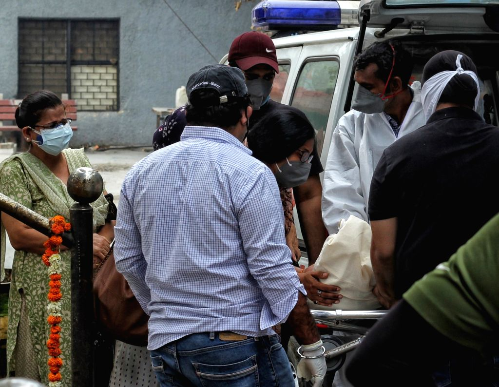 Relatives and Health workers cremation of the body of covid-19 affected victims for last rites at Nigambodh ghat crematorium in New Delhi on Tuesday, 18 May, 2021.