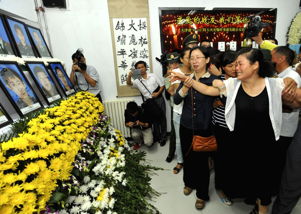 Relatives of deceased firefighters attend a mourning ceremony held at a memorial hall for the firefighters who lost their lives in the massive warehouse blasts in ...