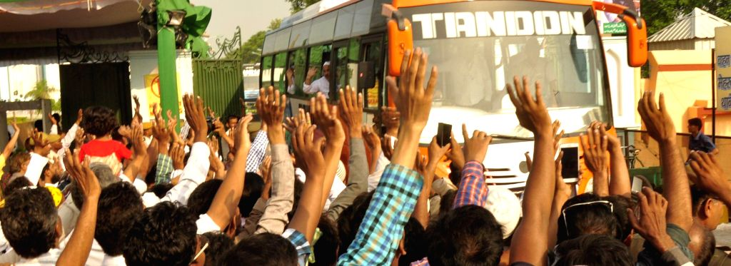 Relatives of Haj pilgrims wave at them as the first batch of pilgrims departs for Mecca from Haj House in Lucknow on Aug 27, 2014.