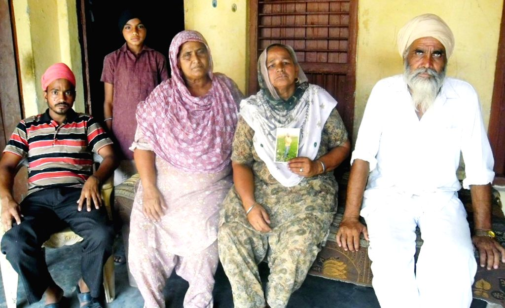 Relatives of Harsimran Singh who is believed to be trapped in the violence-hit Iraqi city of Mosul show his photograph in Amritsar on June 18, 2014. - Harsimran Singh