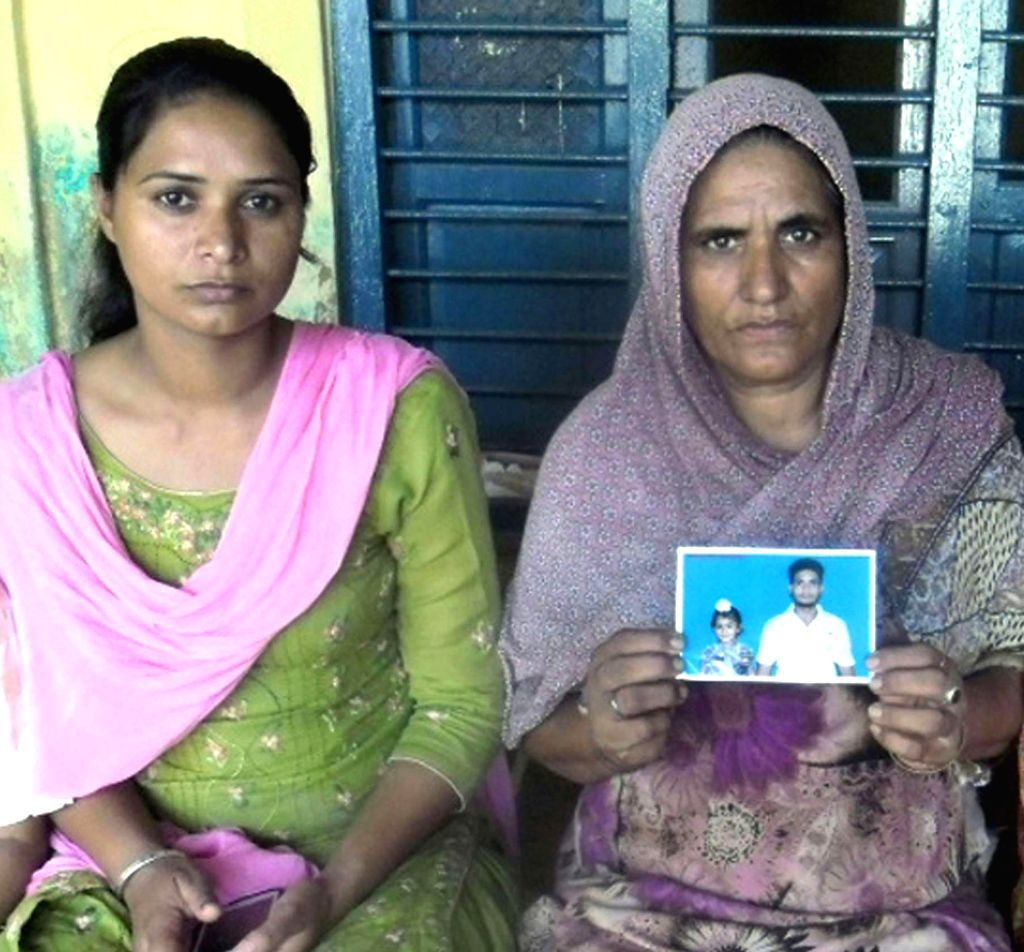 Relatives of Jatinder Singh who is believed to be trapped in the violence-hit Iraqi city of Mosul show his photograph in Amritsar on June 18, 2014. - Jatinder Singh