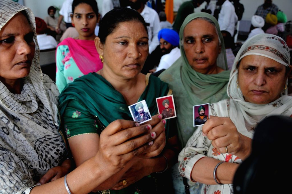 Relatives of the Indian Army soldiers martyred in the Kargil war show their photographs on 20th Anniversary of Kargil Vijay Diwas at the Punjab State War Heroes' Memorial and Museum, in ...