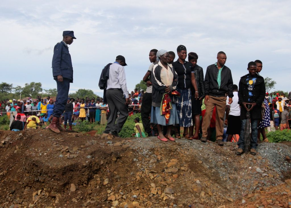 Relatives of trapped miners wait near a flooded shaft at a mine in Battlefields, Mashonaland West Province, Zimbabwe, Feb. 16, 2019. Eleven illegal miners ...