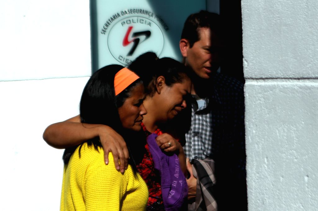 Relatives of victims of a series of street attacks arrive at the Legal Medical Institute in Sao Paul State, Brazil, on Aug. 14, 2015. At least 19 people have died ...