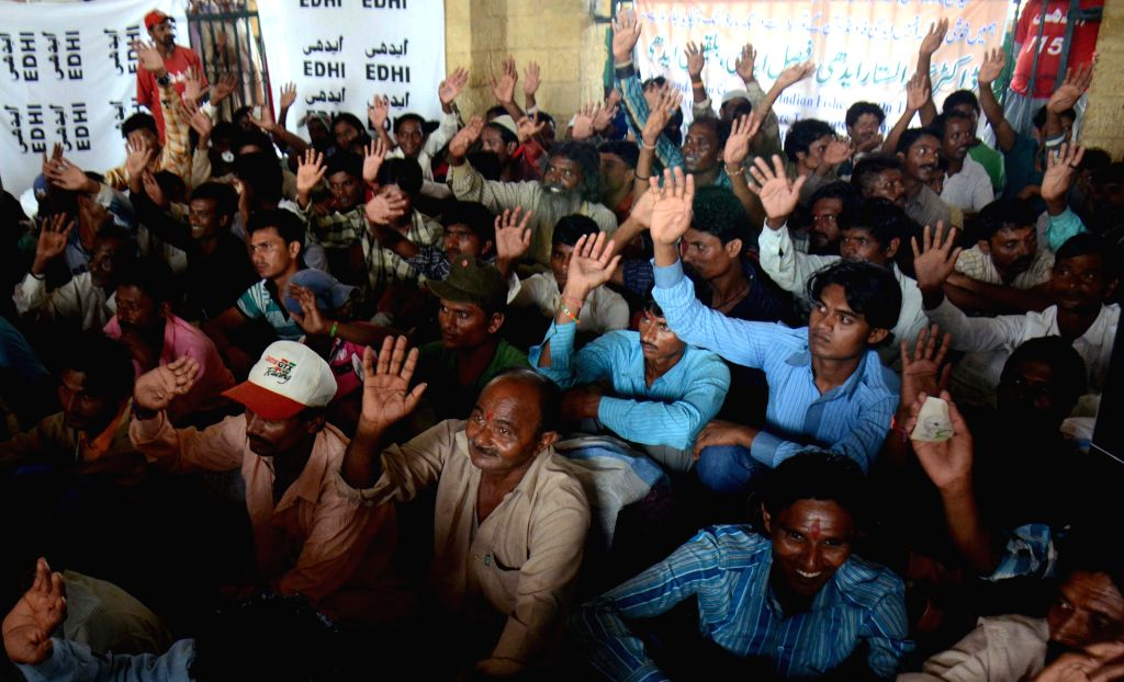 Released Indian fishermen rise their hands as they wait at a railway station in southern Pakistani port city of Karachi, Aug. 2, 2015. Pakistan on Sunday released ...