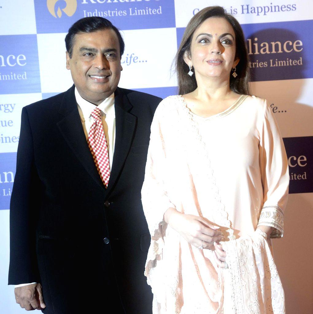 Reliance Industries Ltd (RIL) chairman Mukesh Ambani arrives to attend company's 40th Annual General Meeting (AGM) at Birla Matoshree auditorium with his wife Nita Ambani in Mumbai on June 18, 2014. - Mukesh Ambani and Nita Ambani