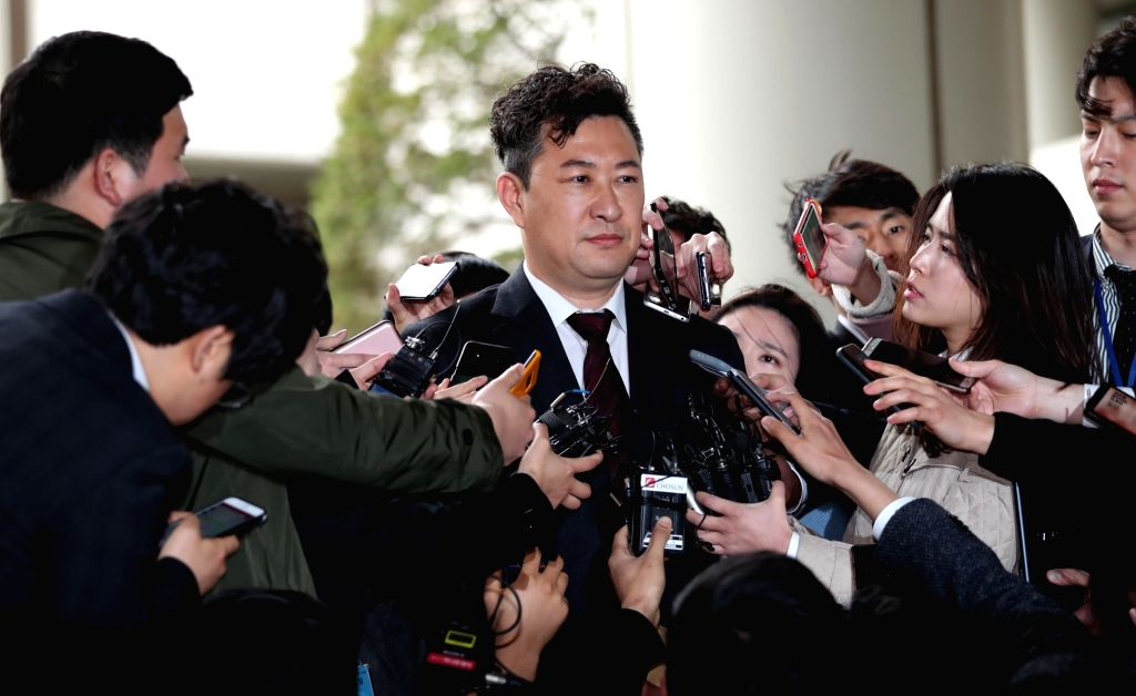 Reporters surround Kang Cheol-koo, court-appointed lawyer for ousted former President Park Geun-hye, as he exits her trial following the verdict at the Seoul Central District Court on April 6, ...