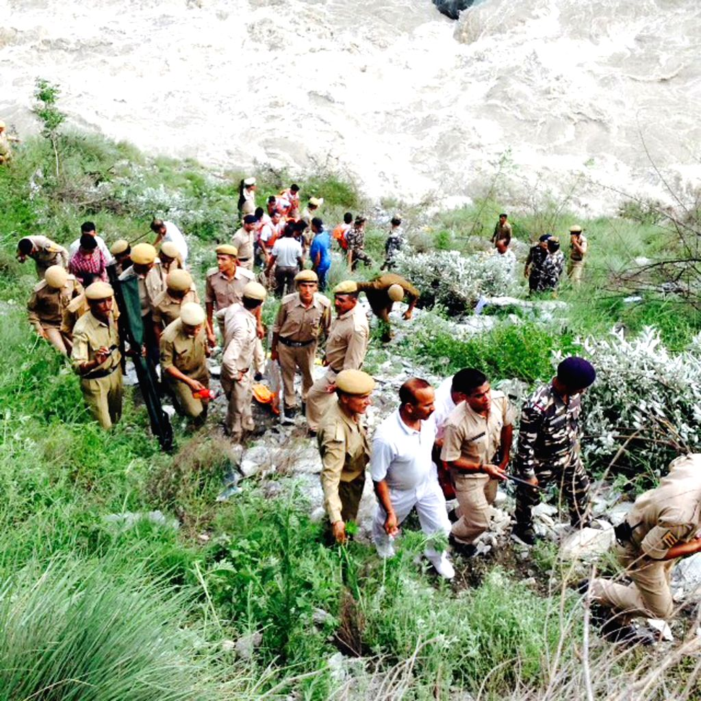 Rescue operations underway at the site where a tourist bus fell into the Parvati river on 23th July in Kullu of Himachal Pradesh on July 24, 2015. At least 20 persons are still missing and 9 ...