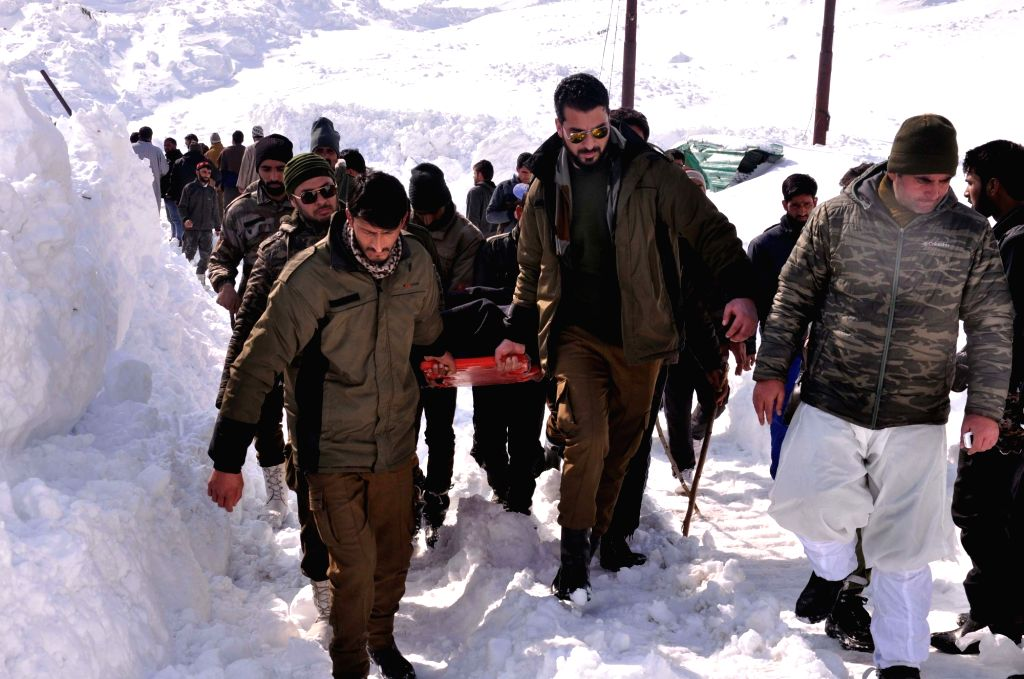Rescue personnel carry a body recovered from a police post that was buried under an avalanche in Jawahar Tunnel area on Jammu-Srinagar highway, on Feb 8, 2019. Seven people were killed and ...