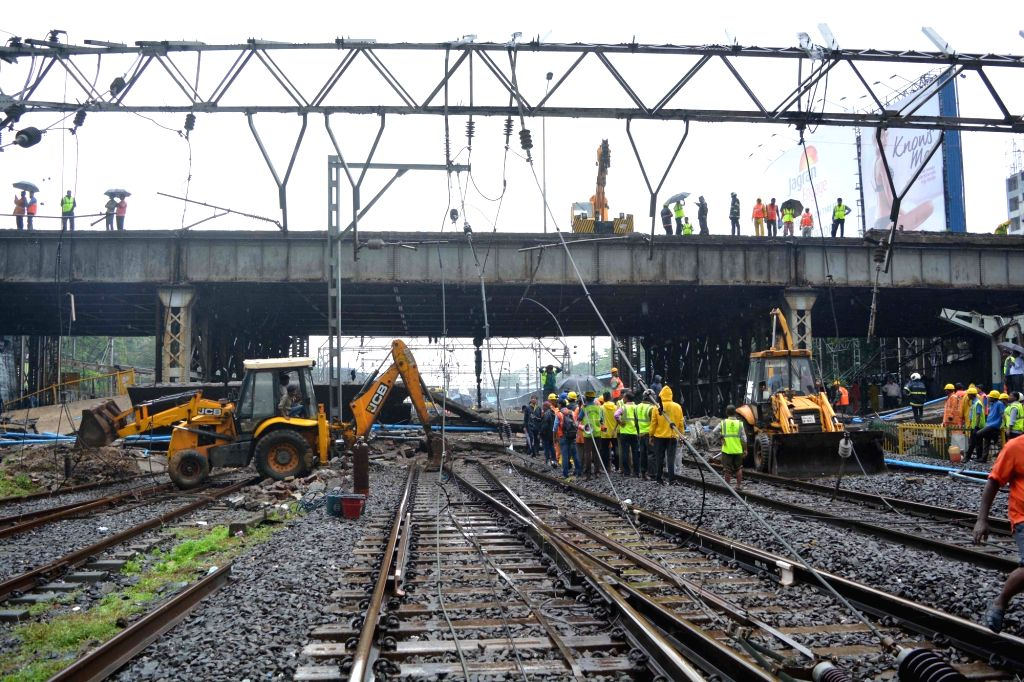 Rescue workers clear the debris after a portion of the Gokhale footover Bridge, running east-west over the Andheri station crashed over the Western Railway (WR) tracks injuring at least ...