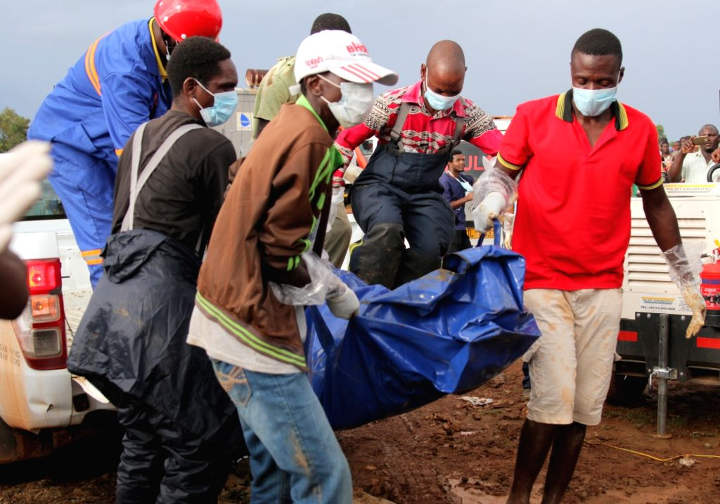 Rescuers carry a miner's body at a mine in Battlefields, Mashonaland West Province, Zimbabwe, Feb. 16, 2019. Eleven illegal miners were rescued Saturday ...