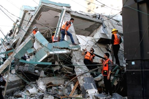 Rescuers check rubbles of Jala Tower, which housed offices of Al-Jazeera TV and Associated Press as well as residential apartments, after it was hit by an Israeli airstrike in Gaza City, on May 15, ...