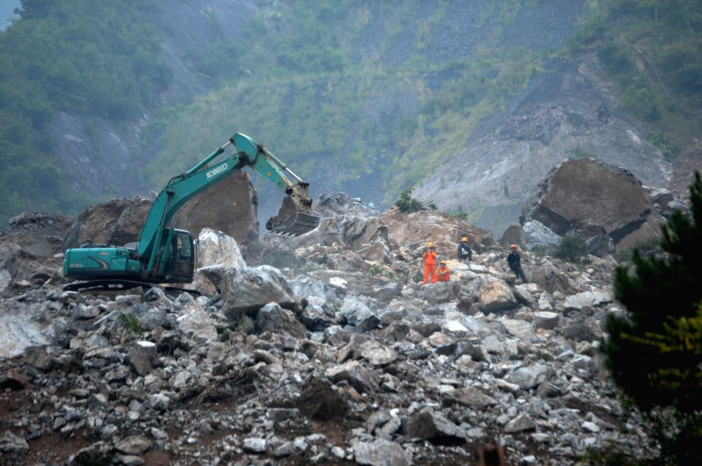 Rescuers clean the landslide site in Shanyang County, northwest China's Shaanxi Province, Aug. 12, 2015. Around 40 people are missing in the landslide hitting the ...