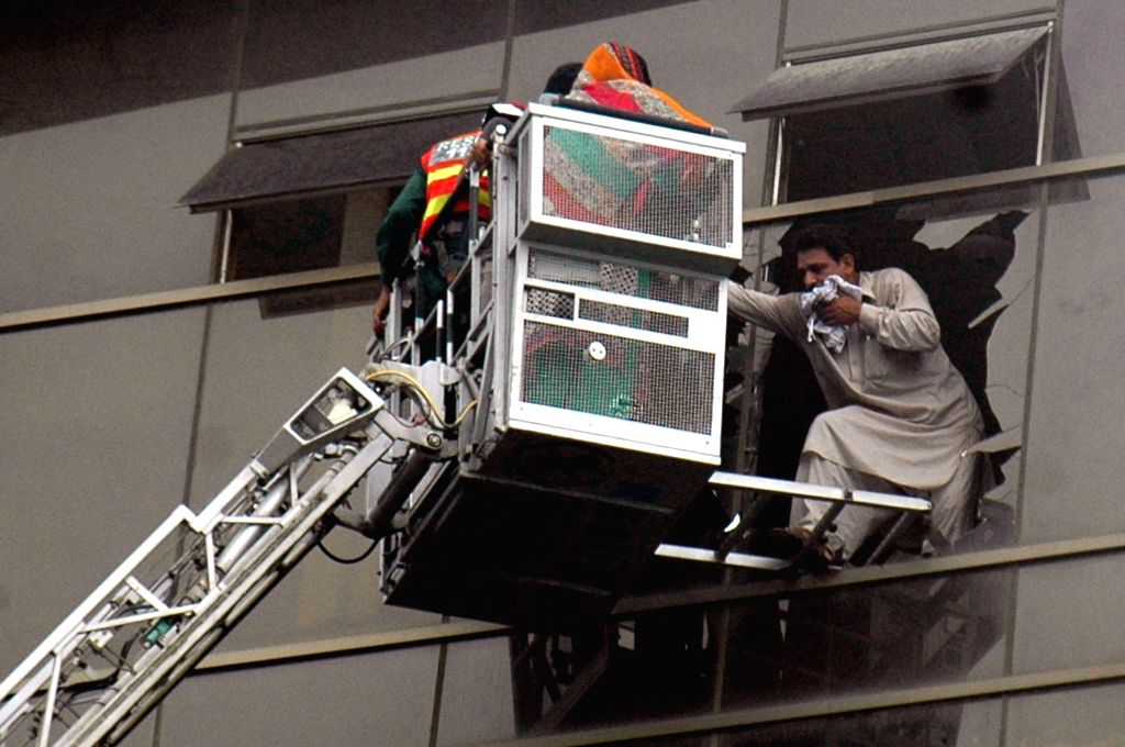 Rescuers evacuate a man from a plaza which caught fire in eastern Pakistan's Lahore, Aug. 11, 2015. At least one man was killed while 11 others injured on Tuesday ...
