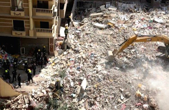 Rescuers search for people under debris of a collapsed building in Cairo, Egypt, March 27, 2021.
