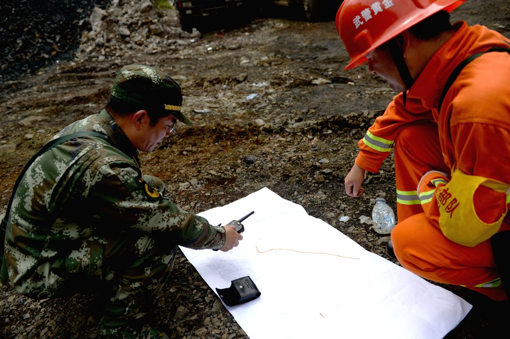 Rescuers survey the terrain of the landslide site in Shanyang County, northwest China's Shaanxi Province, Aug. 12, 2015. Around 40 people are missing in the ...