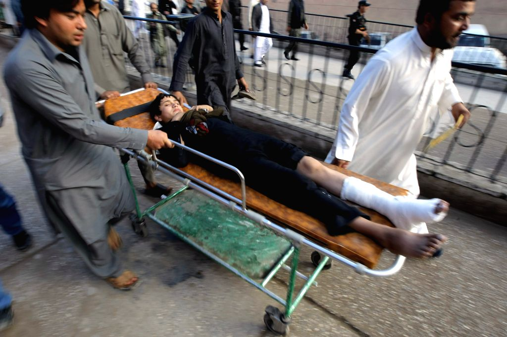 Rescuers transfer a man to hospital in northwest Pakistan's Peshawar, Oct. 26, 2015. The Pakistani government and army has kicked off a rescue and relief operation ...