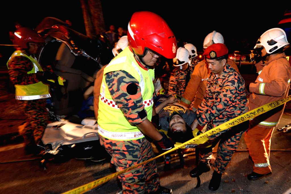 Rescuers transport an injured passenger at the scene of a car accident in Kota Kinabalu in the state of Sabah, Malaysia, Jan. 19, 2016. The car accident ...