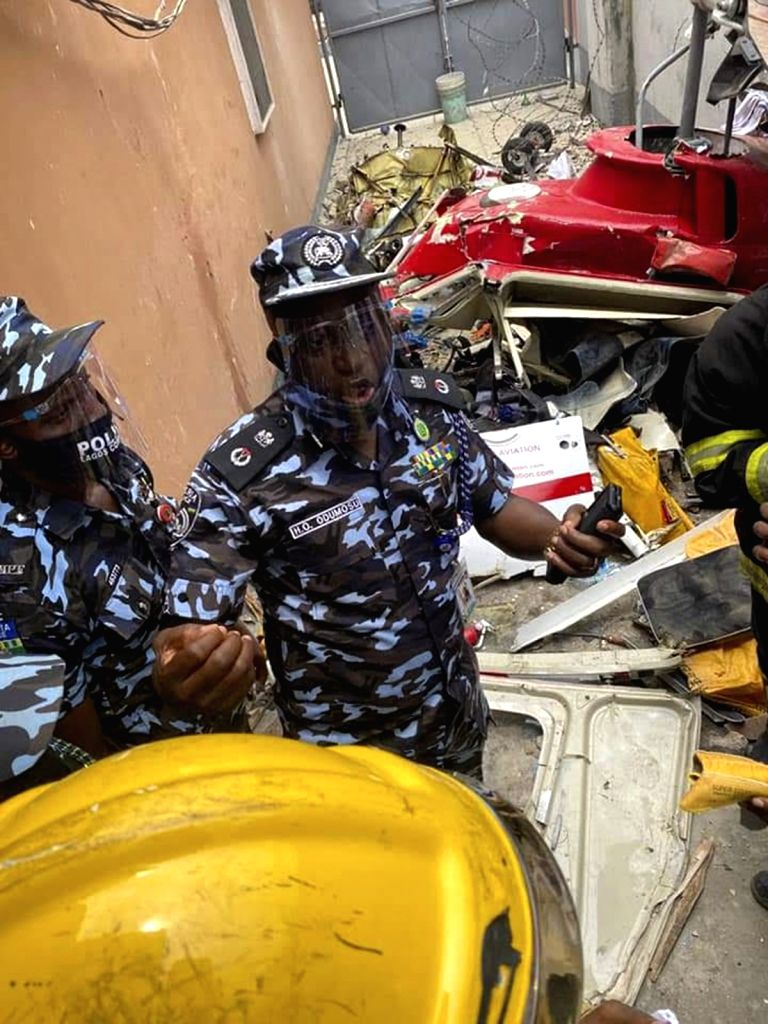 Rescuers work at the scene of a helicopter crash in Lagos, Nigeria, Aug. 28, 2020. Two people were killed and another injured in a helicopter crash in Lagos, ...