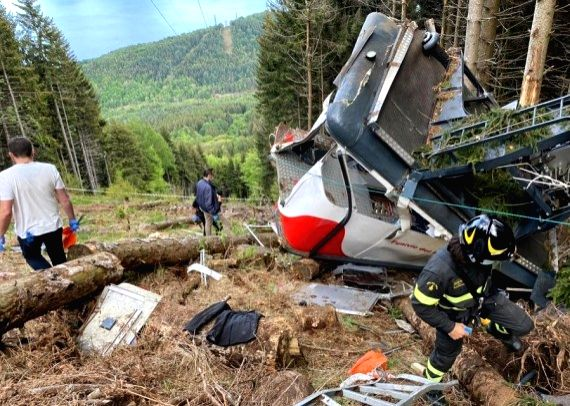 Rescuers work by the wreckage of a cable car after it falls in north Italy's Piedmont region, May 23, 2021.