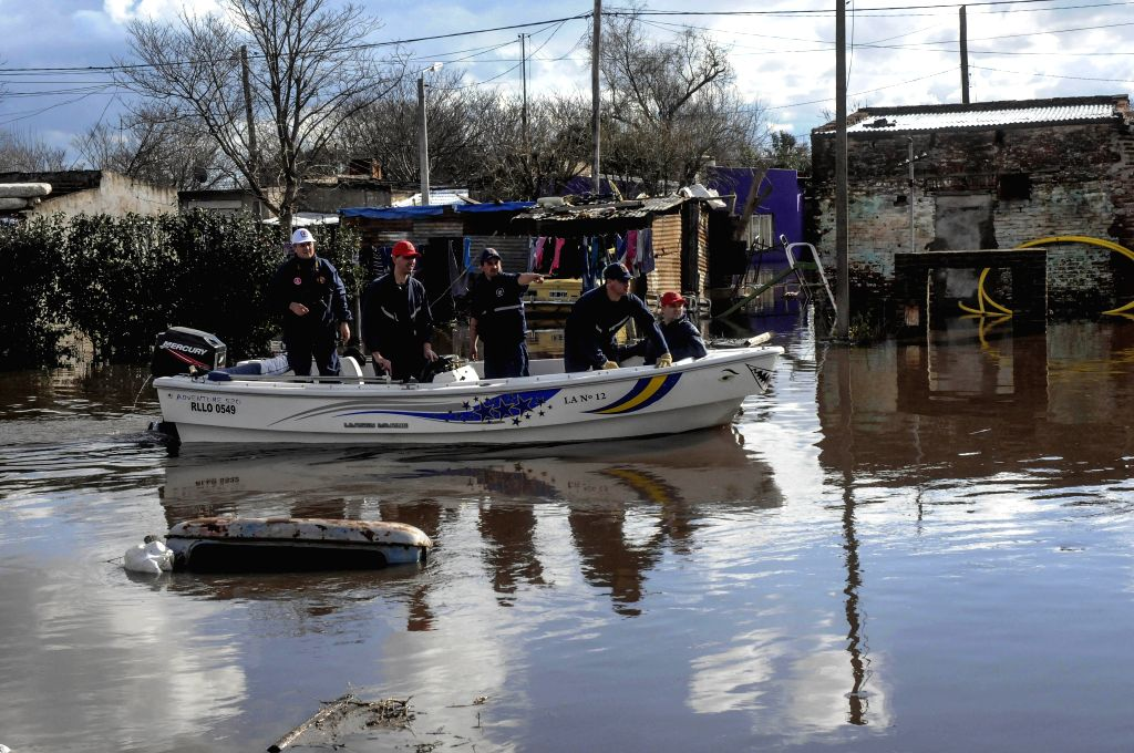 Rescuers work in a flooded road in Salto city, Buenos Aires province, Argentina, on Aug. 11, 2015. According to local press, the heavy rains in the province of Buenos ...