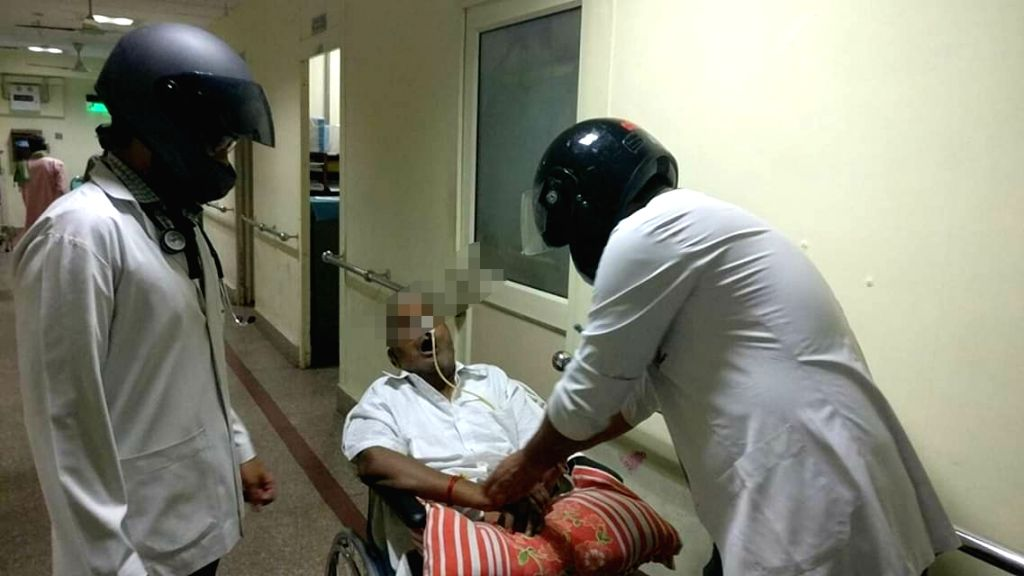 Resident doctors of All India Institute of Medical Sciences (AIIMS)  attend to a patient weraing helmets as a mark of protest against the recent attack on doctors in Kolkata; in New Delhi ...