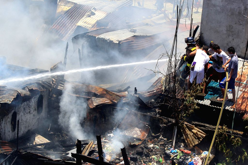 Residents and firefighters put out a fire at a residential area in Paranaque City, the Philippines, Aug. 19, 2015. The fire left 20 families homeless. ...